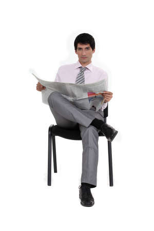 Businessman reading a newspaper Stock Photo - 15391424