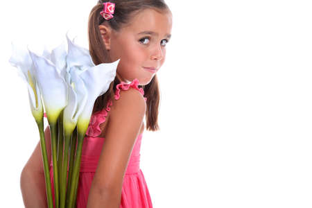 little girl hiding flowers behind her back photo