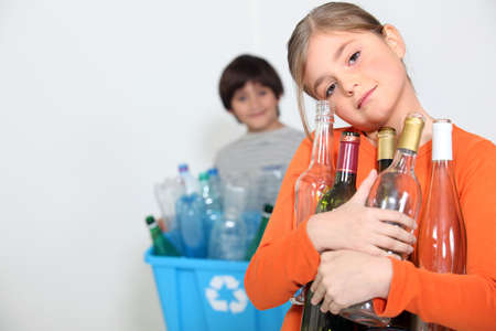 A girl and a boy recycling glass bottles photo