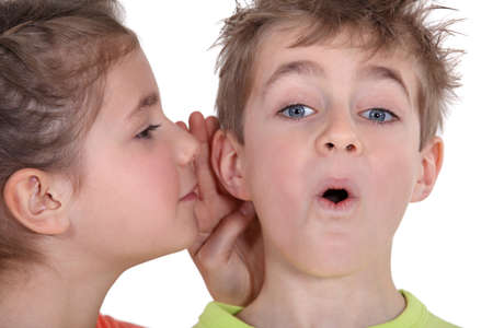 secret: little girl telling his brother a secret