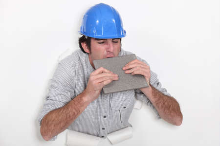 fedup: Fed-up tradesman biting a tile