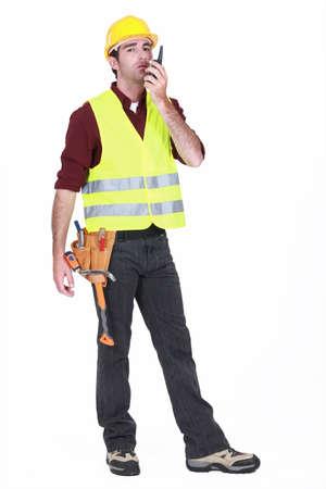 Workman using walkie-talkie on white background Stock Photo - 15391486
