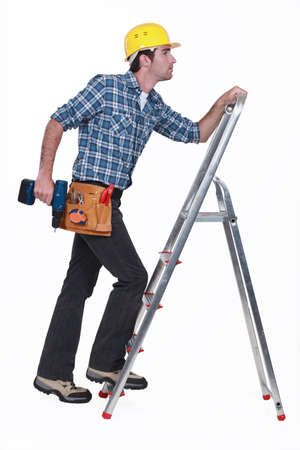 Carpenter with drill climbing step-ladder photo
