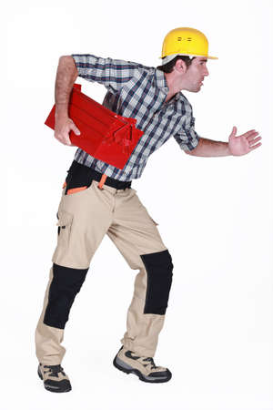chest of drawers: Builder stood in running position holding tool box