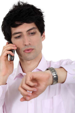 impatient: A businessman over the phone looking at his watch  Stock Photo