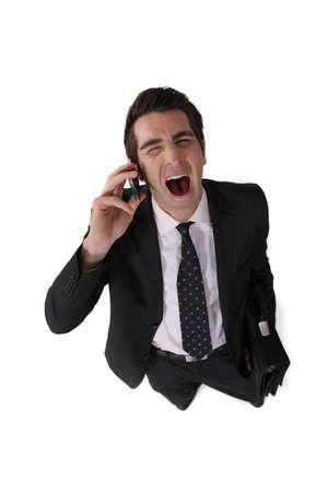 Businessman screaming down the telephone photo