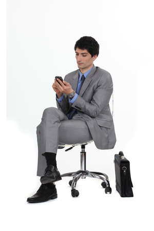 answering: Businessman looking at his cellphone