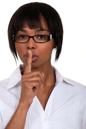guardar silencio: mujer haciendo un signo silencio