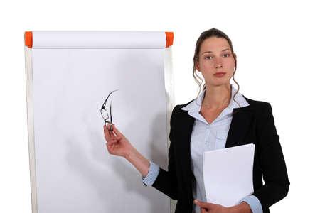 Femme d'affaires debout en face de tableau à feuilles mobiles