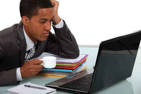 concentrating: An African American businessman drinking a coffee while looking his laptop