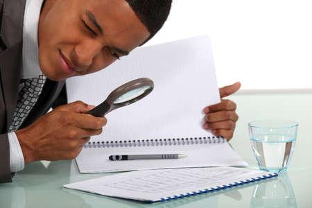 Man de behandeling van een document met een vergrootglas