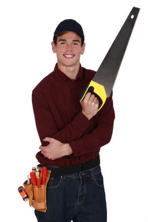 crosscut: Young tradesman holding a saw Stock Photo