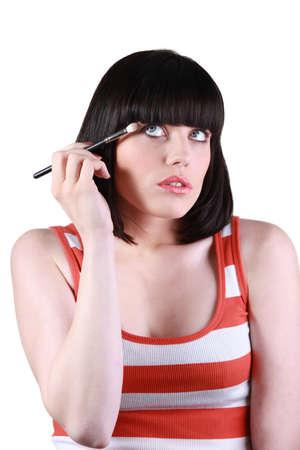 clean cut: Young woman applying eye shadow