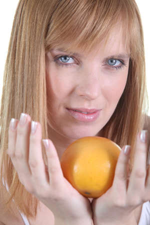 a woman taking an orange in her hands photo