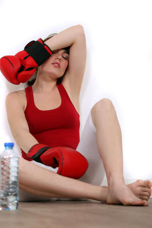Exhausted woman with boxing gloves photo