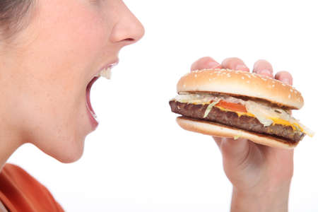 woman open mouth: Woman eating cheeseburger