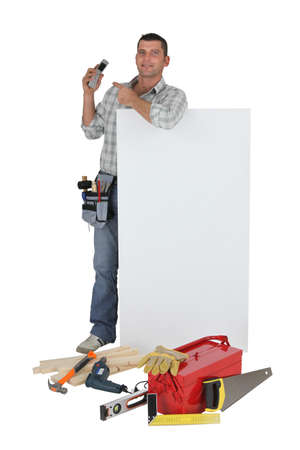 Carpenter pointing to mobile telephone whilst stood by blank poster photo