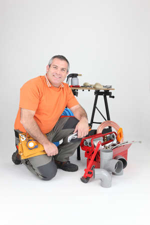 Plumber kneeling by equipment photo