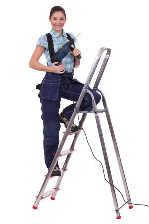 servicewoman: A servicewoman with a driller on a ladder. Stock Photo