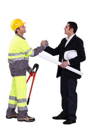 businessman and craftsman shaking hands photo