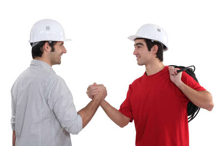 greets: Tradesman welcoming a new recruit Stock Photo