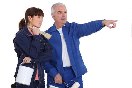 tradespeople: Painter telling his assistant which area to paint