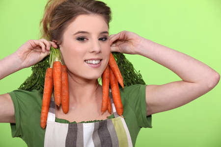 Funny woman holding carrots to her ears photo
