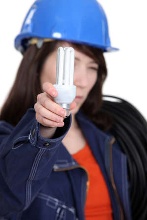 emit: Electrician holding a compact fluorescent lamp
