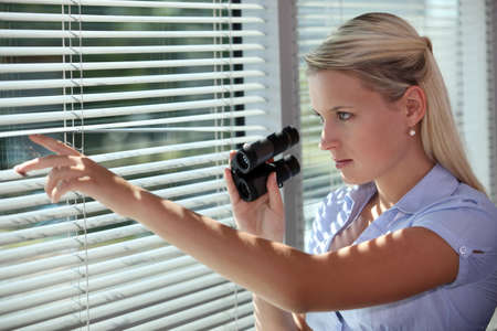 stalking: woman looking through the blinds with binoculars