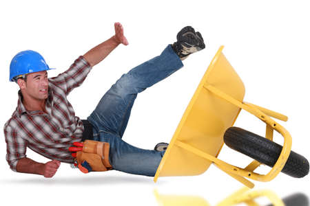 Laborer tumbling down from a barrow Stock Photo