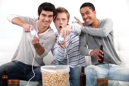 jugando videojuegos: Tres adolescentes masculinos que juegan juegos de video. Foto de archivo