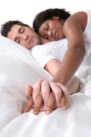 metis: Young couple asleep holding hands in bed Stock Photo