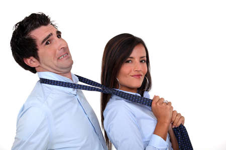 seducing: Woman grabbing man by tie Stock Photo