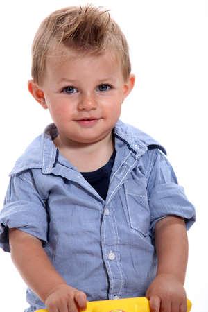 12 18 months: Closeup of a little boy with gelled hair using a walker Stock Photo
