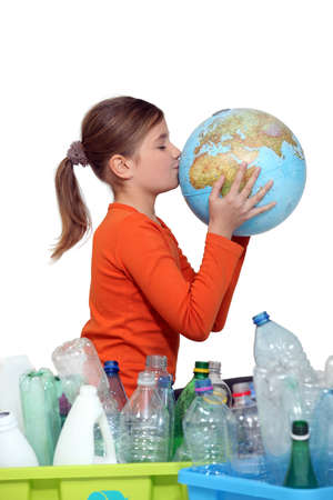 water recycling: Little girl kissing planet earth next to her recycling