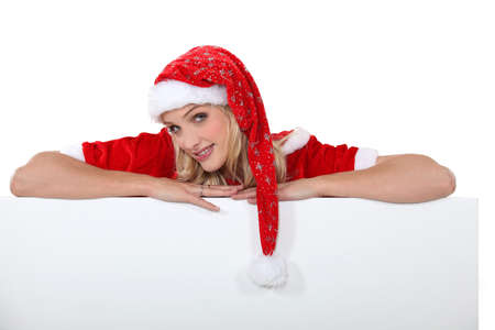 mrs claus: Lady Santa with a board left blank for your message Stock Photo