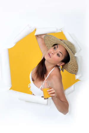 bursting: Woman with orange juice bursting out of a paper screen Stock Photo