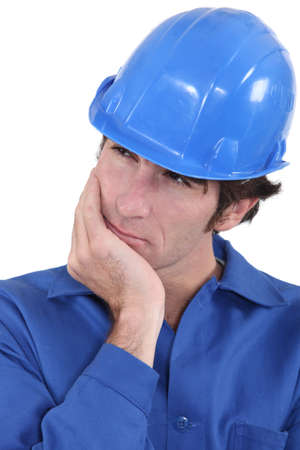 Builder having a good think about what to do next photo