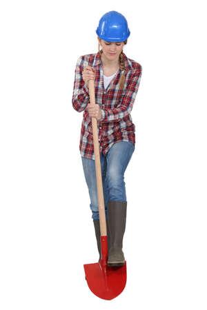 Female laborer digging with a shovel, studio shot photo