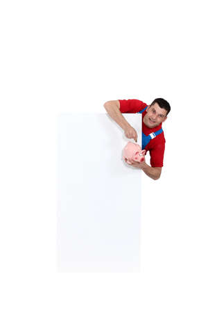 Tradesman pointing to a piggy bank and standing beside a blank sign Stock Photo - 15410488