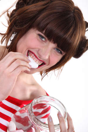 A woman eating marshmallows. photo