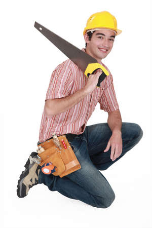 carpenter with saw kneeling Stock Photo - 15411084