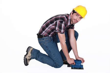 laborious: Tradesman using a sander Stock Photo