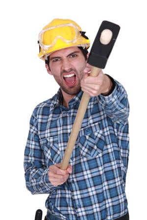 trineo: Un trabajador de la construcción enojado con un mazo. Foto de archivo