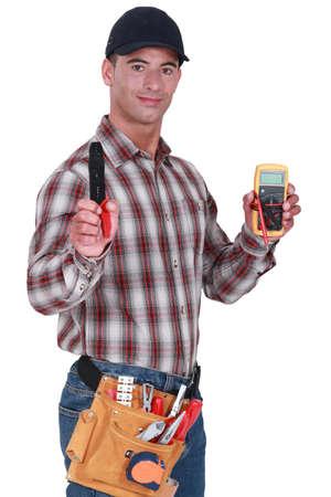 technical service: Craftsman with tweezers and voltmeter Stock Photo