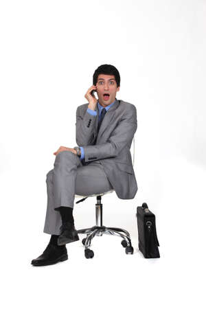 portrait of businessman sitting on swivel chair looking amazed photo