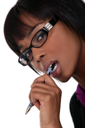 Businesswoman wearing glasses and chewing a pen photo
