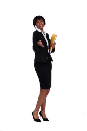 business woman standing: Friendly businesswoman holding her hand out for a handshake Stock Photo