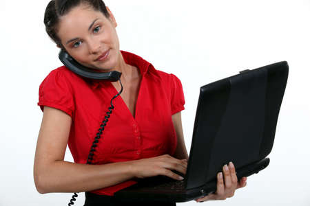 landline phone: A busy businesswoman. Stock Photo