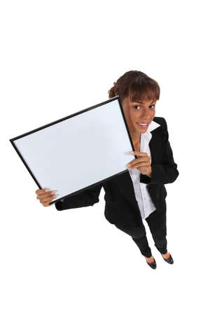 trouser: Woman in a trouser suit holding a blank board Stock Photo